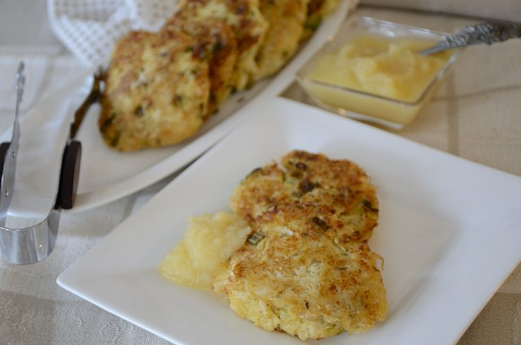 Fried sauerkraut cakes on a plate with a dollop of applesauce.