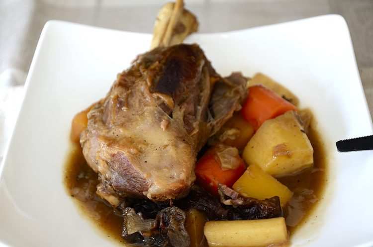 Lamb shanks in Guinness in a bowl with root vegetables.