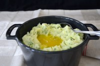 Casserole of mashed potatoes with green onions and parsley mixed in and a well of melted butter in the center.