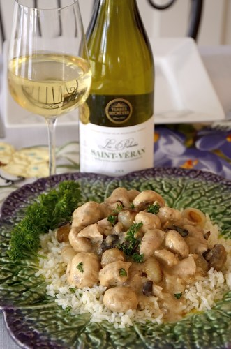 Close up of French rabbit in mustard sauce with pearl onions and mushrooms on a bed of rice with a bottle and glass of Chardonnay beside.