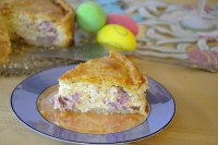 Piece of Italian Easter Pie on a plate with Easter eggs around the table.