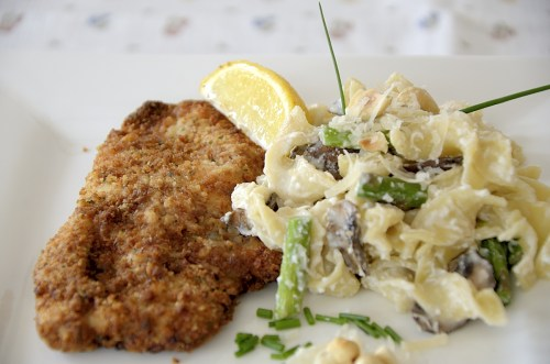 Crispy air fried chicken cutlets with a slice of lemon on a plate.