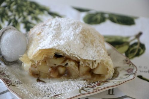 Flaky apple strudel with phyllo pastry topped with icing sugar on a plate.