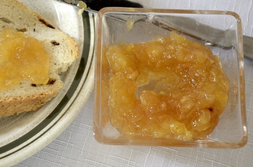 Small bowl of pineapple jam beside toast on a plate.