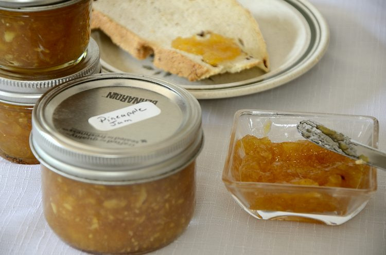 Small bowl of pineapple jam beside toast on a plate with a jar of jam on the side.