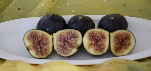 Fresh Black Mission Figs on a plate with some cut in half.