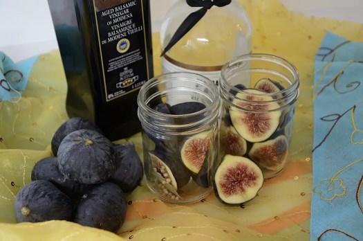 2 half pint jars of figs with balsamic vinegar and coarse sea salt beside them.