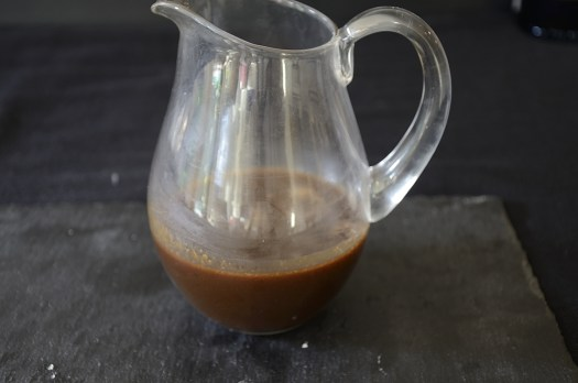 Pitcher of chocolate brown balsamic caramel sauce.