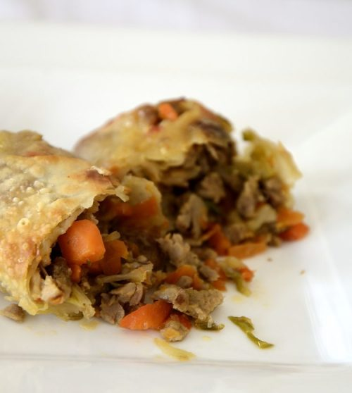 Crispy egg roll cut open to show cabbage, bean sprout and pork filling.
