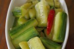 Glistening cucumber spears with a Thai red chili in a serving dish.