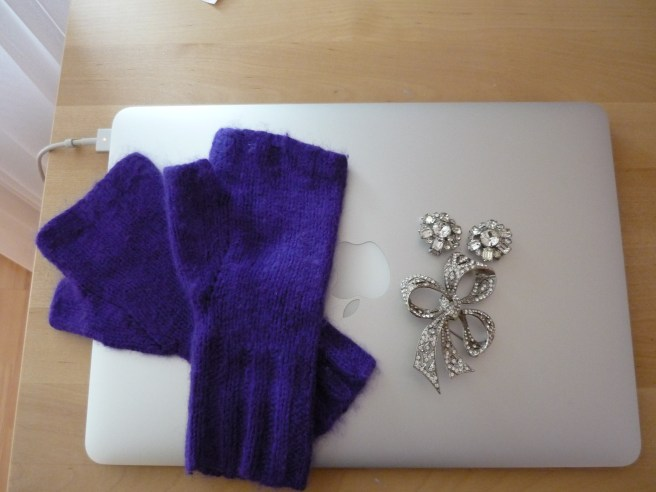 closed Mac laptop with fingerless purple mittens and sparkly jewelry