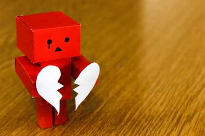 red figurine with a tear in his eye, holding out a broken heart persistent depressive disorder