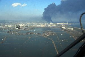 An aerial view of damage in the Sendai region with black smoke coming from the Nippon Oil Sendai oil refinery. Credit: Wikimedia Commons
