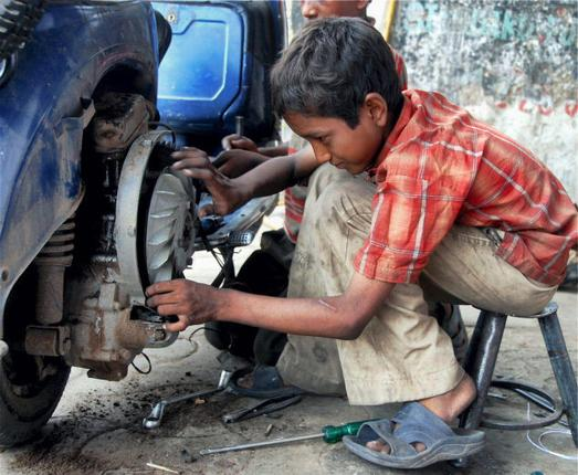 A child repairs a scooter on the outskirts of Ahmedabad: PTI