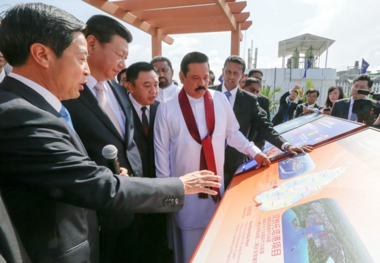 """Mahinda Rajapaksa briefing President Xi Jinping of China about the graphical illustrations of the """"Colombo Port City"""" project at the official commissioning ceremony in September 2014. The port city project is the largest foreign-funded investment in Sri Lanka's history."""