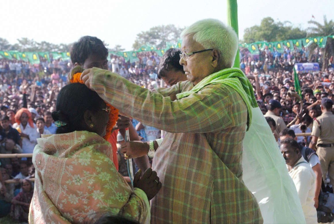 RJD chief Lalu Prasad welcomes a woman during an election rally at Jeevdhara, East Champaran, Bihar on Friday. Credit: PTI