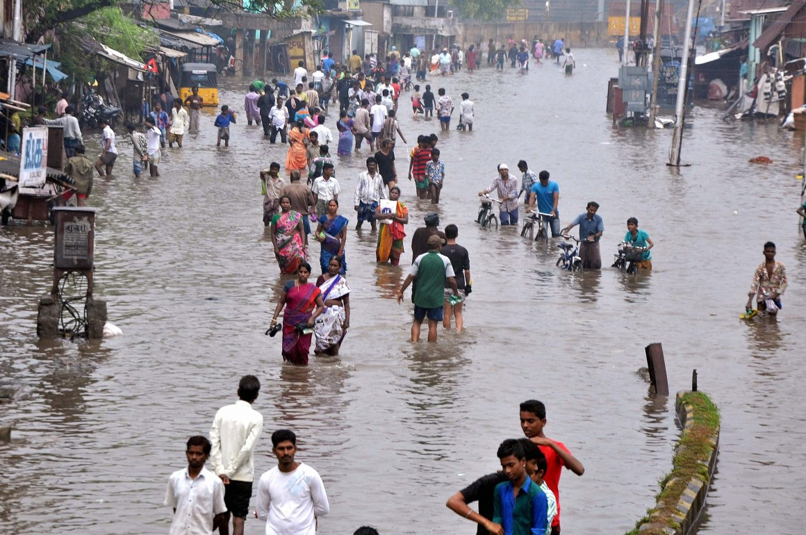 Chennai: People wade through a waterlogged road following heavy rains at Vyasarpadi in Chennai on Friday. PTI Photo (PTI11_13_2015_000295B)