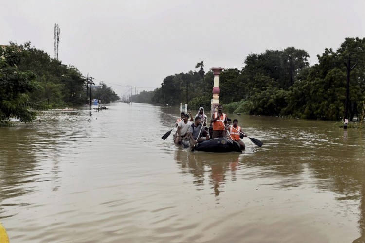 Rescue workers transport evacuees in a rubber boat through floodwaters following heavy rains in Chennai on Wednesday. Credit: PTI