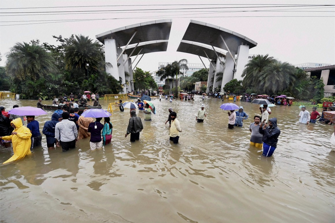 People wade through a waterlogged road following heavy rains at Porur in Chennai on Wednesday. Credit: PTI