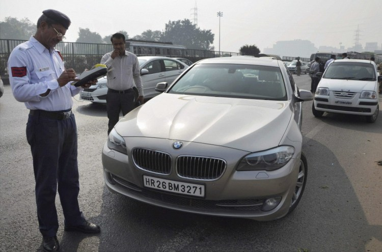 Delhi Traffic Police issue a ticket to a motorist on the Delhi Gurgaon expressway for violating the Odd- Even scheme on Monday. Credit: PTI