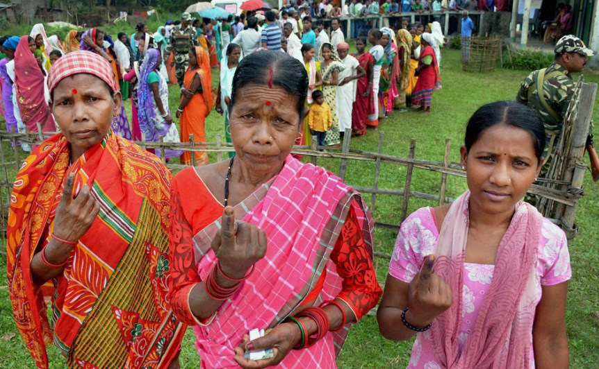 Tea tribe women show their inked fingers after casting their vote during the first phase of the Assembly Elections for Duliajan Assembly Constituency at Bordubi in Assam on Monday. Credit: PTI