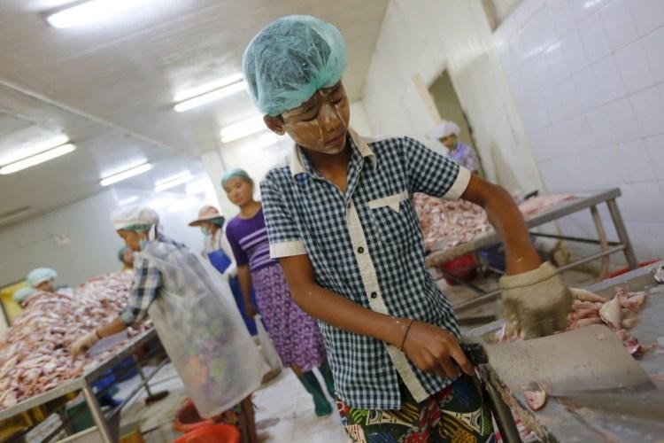 A boy chops fish at a seafood export factory in Hlaingthaya Industrial Zone, outside Yangon, Myanmar February 19, 2016. Credit: Reuters/Soe Zeya Tun