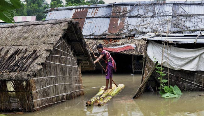 A woman crosses a flooded area over a raft made of banana tree trunks at Bura Bure in Morigaon district of Assam on Sunday. Credit: PTI