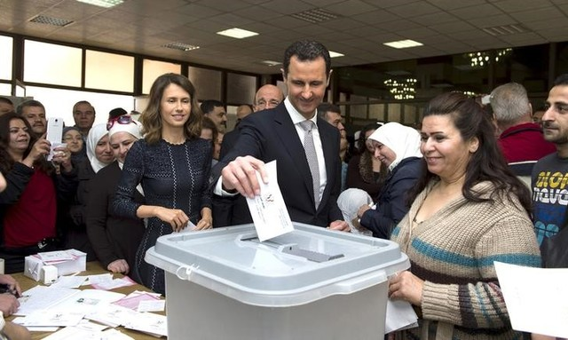 Syria's President Bashar al-Assad (C) casts his vote next to his wife Asma (centre left) inside a polling station during parliamentary elections in Damascus, Syria, in this handout picture provided by SANA on April 13, 2016. REUTERS/SANA/Handout via Reuters