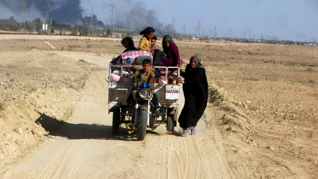 Civilians who fled their homes due to the clashes between Iraqi security forces and Islamic state militants move through the town of Hit in Anbar province, April 4, 2016. Credit: REUTERS/Stringer