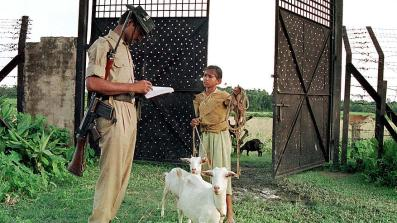 An Indian Border Security Force (BSF) guard at a checkpoint separating India and Bangladesh in the state of Assam verifies the name of a girl who went to graze her goats on the other side of the border. Credit: Reuters