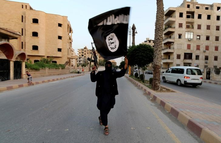 A member loyal to Islamic State waves a flag in Raqqa June 29, 2014. Credit: Reuters/Stringer/Files.