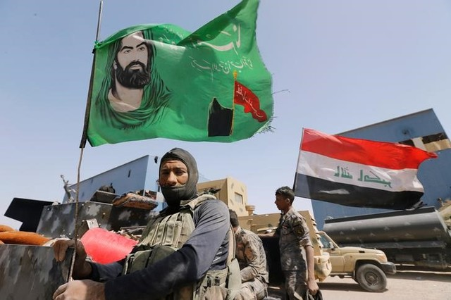 A Shi'ite fighter stands next to a religious flag near Falluja, Iraq, May 24, 2016. Credit: Reuters/Thaier Al-Sudani