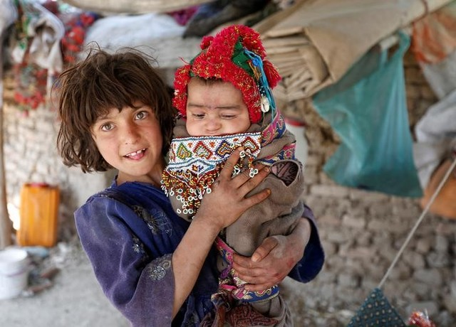 An internally displaced Afghan girl holds a child at a refugee camp in Kabul, Afghanistan May 31, 2016. Credit: Reuters/Mohammad Ismail