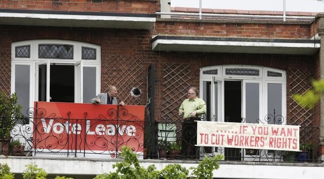 Neighbours Tony (L) and Frank pose for cameras after hanging rival EU referendum banners from their balconies in north London, May 25, 2016. Credit: Reuters/Neil Hall