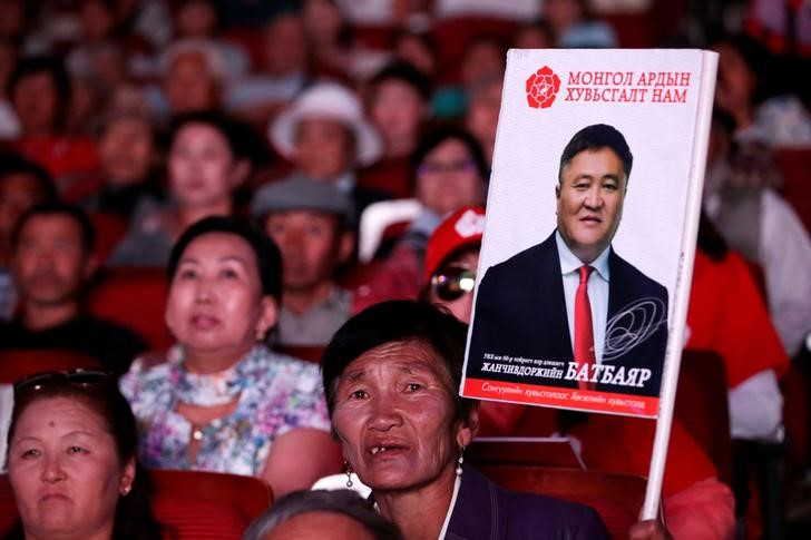 A woman holding a picture of a candidate from Mongolian People's Revolutionary Party (MPRP) attends a rally for the upcoming parliamentary elections in Ulan Bator, Mongolia, June 26, 2016. Credit: Reuters/Jason Lee