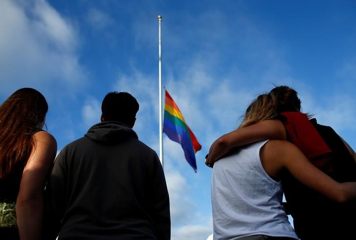 Mourners gather under a LGBT pride flag flying at half-mast for a candlelight vigil in remembrance for mass shooting victims in Orlando, from San Diego, California, US. June 12, 2016. Credit: Reuters/Mike Blake/File Photo