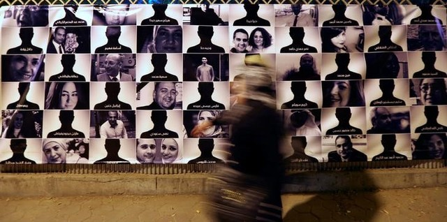 A woman passes by photos of EgyptAir flight 804 victims, at the Cairo Opera House in Cairo, Egypt May 26, 2016. Credit: Reuters/Mohamed Abd El Ghany