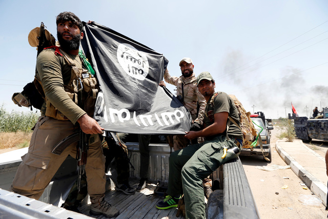 Shi'ite fighters hold an Islamic State flag which they pulled down as they celebrate victory in the town of Garma, Iraq. Credit: Reuters/Thaier Al-Sudani