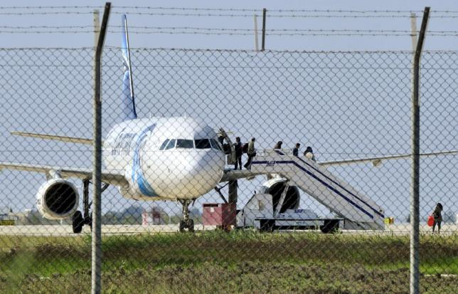 Passengers evacuate a hijacked EgyptAir Airbus 320 plane at Larnaca airport, Cyprus, March 29, 2016. Credit: Reuters/Stringer.