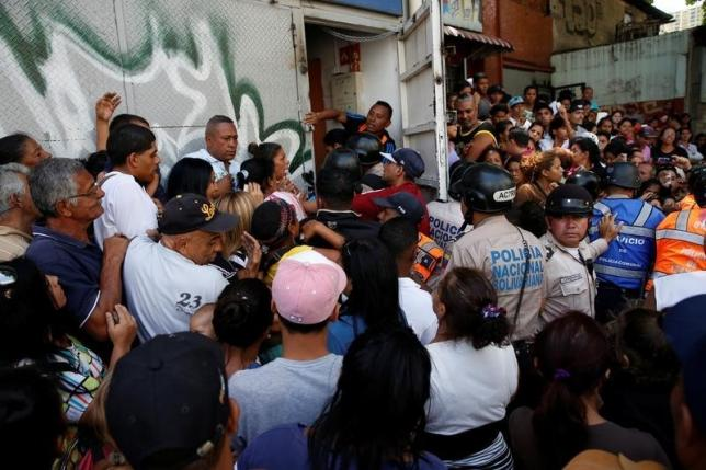 People gather to try to buy pasta while riot police try to control the crowd outside a supermarket in Caracas, Venezuela, June 10, 2016. Credit: Reuters/Carlos Garcia Rawlins