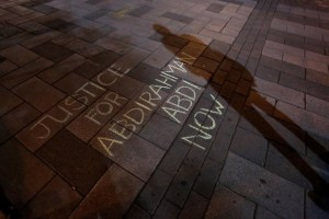 A man casts a shadow near a message written in chalk during a vigil for Abdirahman Abdi, a Somali immigrant to Canada who died after being hospitalized in critical condition following his arrest by Canadian police, in Ottawa, Ontario, Canada, July 26, 2016. Chris Wattie, Reuters/ Files