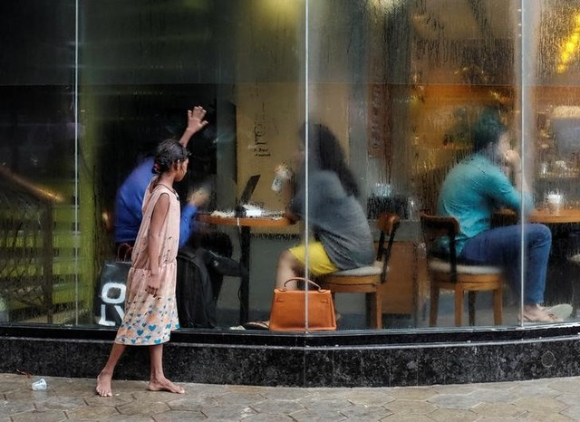 A homeless girl asks for alms outside a coffee shop in Mumbai, India, June 24, 2016. REUTERS/Danish Siddiqui/Files