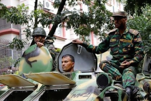 Army soldiers atop an armored military vehicle drive near the Holey Artisan restaurant after Islamist militants attacked the upscale cafe in Dhaka