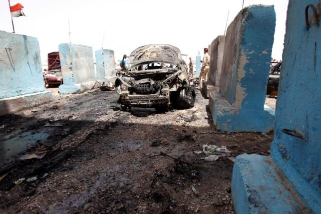 A destroyed vehicle is seen at the site of a suicide bomb attack at a checkpoint in Rashidiya, a district north of Baghdad, Iraq July 13, 2016. REUTERS/Khalid al Mousily