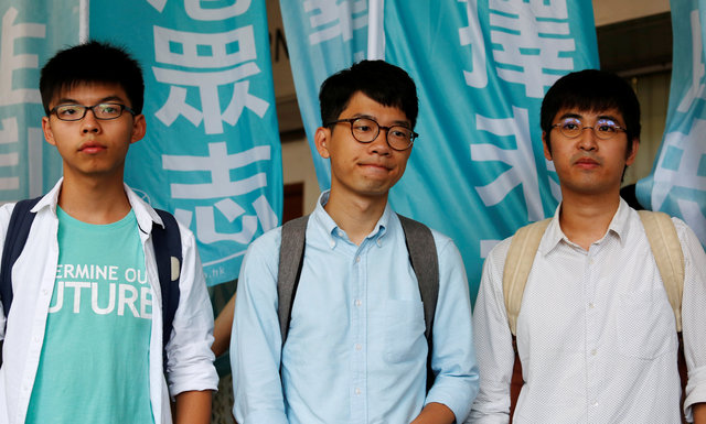 "Student leaders (L-R) Joshua Wong, Nathan Law and Alex Chow pose before a verdict, on charges of inciting and participating in an illegal assembly in 2014 which led to the ""Occupy Central"" pro-democracy movement, outside a court in Hong Kong July 21, 2016. Credit: Reuters/Bobby Yip"