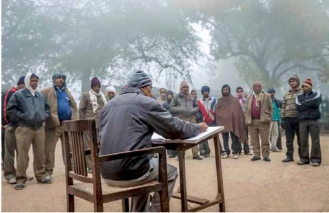 Contract workers at roll call on a winter morning. Credit: Narendra Bisht