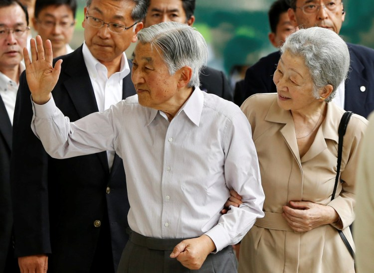 Japan's Emperor Akihito (L), flanked by Empress Michiko, waves to well-wishers as they board a Shinkansen bullet train to depart to their imperial summer villa in Nasu, at Tokyo station in Tokyo, Japan July 25, 2016. Credit: REUTERS/Issei Kato