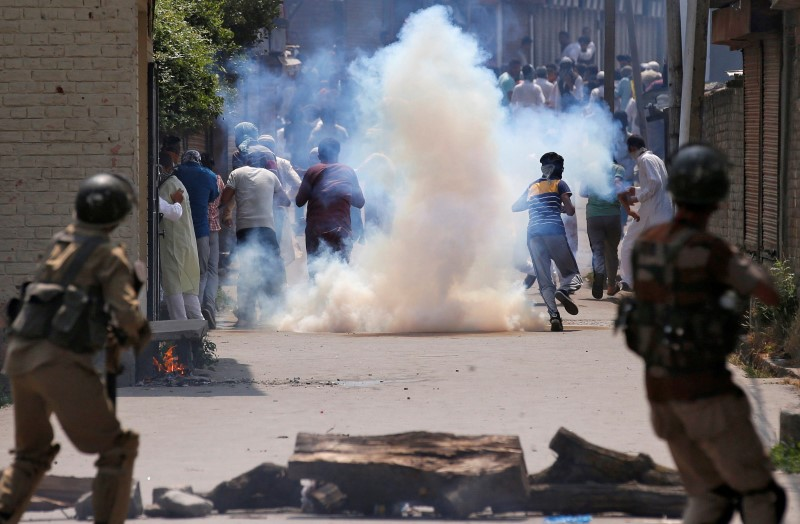 Demonstrators run for cover amid tear gas smoke fired by Indian police during a protest in Srinagar, July 6, 2016. Credit: Reuters/Danish Ismail