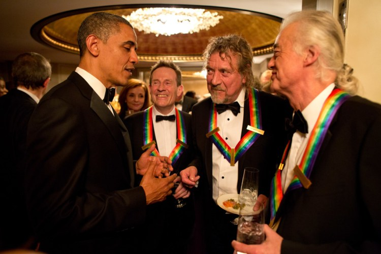 US President Barack Obama chatting with the surviving members of Led Zeppelin – John Paul Jones, Robert Plant and Jimmy Page – during intermission at the Kennedy Center Honors in 2012. Credit: Official White House Photo by Pete Souza/Wikimedia Commons