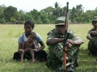 A small child and a woman sit next to LTTE cadres training in a public playground in Kilinochchi, a district in the Northern Province, in this picture taken in June 2004. The Tigers held sway over all aspects of life in areas they controlled until their defeat in 2009. Credit: Amantha Perera/IPS